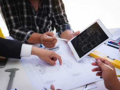 Close up of civil male engineer asian working on blueprint architectural project at construction site at desk in office.