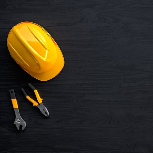 drill, helmet, hammer, pliers and construction tools on black wooden background